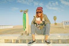 Skateboradåkareflicka med skateboarden och smartphonen Royaltyfria Bilder