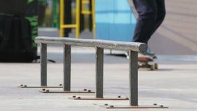 Skateboradåkaren tar en skateboard och försöker tricket på stången i skatepark, slowmo stock video