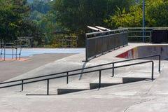 Skatepark vuoto a mezzogiorno con le rampe e le rotaie di frantumazione immagine stock libera da diritti