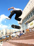 Skater 360 Flipping at a Contest. An action shot of a skater doing a hard trick (360 flip) over a set of stairs at a contest. The crowd is blurry in the Royalty Free Stock Image