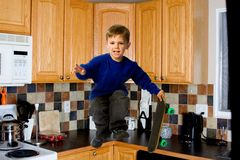 Skater boy. Young boy skate boarding in the kitchen Stock Photo