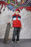 Skater boy in front of wall Royalty Free Stock Photo