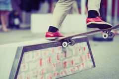 Skater boy rides on summer skate contest outdoor. Teenager skater boy grinding on box in skatepark outdoor.Extreme summer sports background.Feet of teen athlete Stock Photography