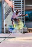 Skater con el polvo colorido del holi Foto de archivo libre de regalías