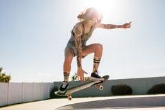 Skater das mulheres que faz o ollie no skate fotos de stock