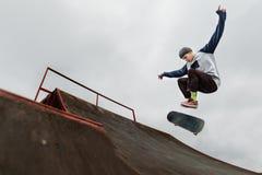 Skater del adolescente en un casquillo que hace un salto del truco en un medio tubo en un fondo del cielo nublado Fotos de archivo libres de regalías
