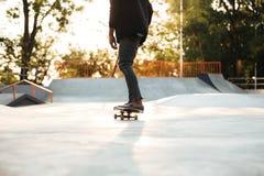 Skater del hombre joven en el monopatín en el parque de la ciudad Foto de archivo libre de regalías