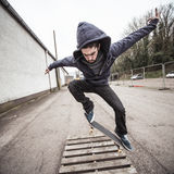 Skater doing ollie over wooden crate Stock Photos