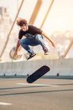 Skater doing tricks and jumping on the street highway bridge. Fr Stock Images
