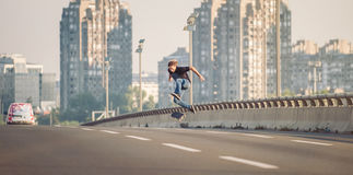Skater doing tricks and jumping on the street highway bridge. Pa Stock Photos