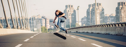 Skater doing tricks and jumping on the street highway bridge. Pa. Skater doing tricks and jumping on the street highway bridge, through urban traffic. Free stock photo