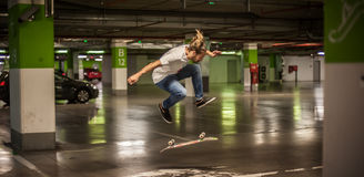 Skater doing tricks and jumping in the underground garage Stock Photos