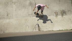 Skater elegante que hace truco del monopatín en la pared vieja almacen de metraje de vídeo
