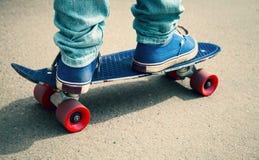 Skater en los gumshoes que se colocan en su patín Imagen de archivo libre de regalías