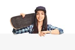 Skater fêmea novo que levanta atrás de um painel Imagem de Stock