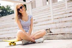 Skater fêmea que senta-se no patim fora imagens de stock