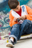 Skater fresco que repara seus auriculares foto de stock