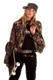 Skater Girl. Blond teenage sk8ter chic in camo jacket, black shirt and knit cap carrying her skateboard and bag Royalty Free Stock Photography
