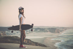 Skater Girl. Beautiful fashion skater girl posing with  a skate board Royalty Free Stock Photo