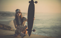 Skater Girl. Beautiful fashion skater girl posing with  a skate board Royalty Free Stock Image
