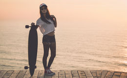 Skater Girl. Beautiful fashion skater girl posing with  a skate board Stock Image