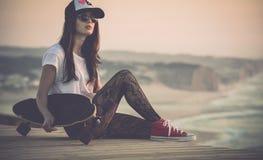 Skater Girl. Beautiful fashion skater girl posing with  a skate board Stock Photos