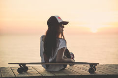 Skater Girl. Beautiful fashion skater girl posing with a skate board royalty free stock images
