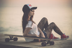 Skater Girl. Beautiful fashion skater girl posing with  a skate board Stock Images