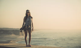 Skater girl. Beautiful and fashion young woman posing at the sunset with a skateboard Stock Photo
