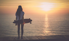 Skater Girl. Beautiful girl with a skateboard looking to the sunset Stock Photo
