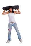 Skater girl holding skateboard behind her head Stock Images