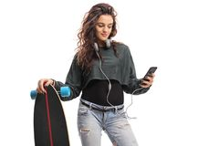 Skater girl with a longboard using a phone Royalty Free Stock Image