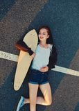 Skater girl lying down on asphalt surface of the road and enjoing summer warm weather after phisical activity Royalty Free Stock Photography