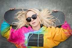 Skater Girl Lying Down. Blond skater girl laying down with board royalty free stock photo