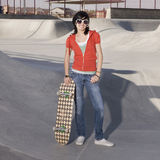 Skater girl at a park. Girl with skateboard and funky sunglasses at the park Royalty Free Stock Photos
