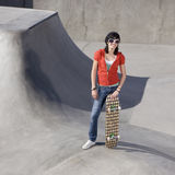 Skater girl at a park. Girl with skateboard and funky sunglasses at the park Royalty Free Stock Image
