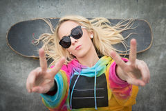 Skater Girl Peace Sign. Blond teen skater girl giving peace sign royalty free stock photos