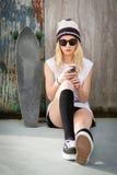 Skater Girl Text Messaging. Pretty blond skater girl text messaging listening to music Royalty Free Stock Image