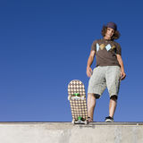 Skater at halfpipe. Skateboarder stands atop half pipe with his skateboard Royalty Free Stock Photo