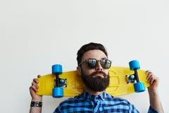 Skater hermoso, sosteniendo un monopatín detrás de su cabeza Fotografía de archivo