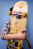 Skater hiding behind his skateboard. On blue background Stock Images