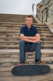 Skater and his board. California skateboarder seated on slate stairs holding board across feet Stock Photography