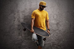 Skater holding longboard and leaning against wall. Skater holding a longboard and leaning against a rusty gray wall Royalty Free Stock Images