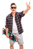 Skater holding skateboard and making a peace sign. Vertical shot of a young male skater holding a skateboard and making a peace hand gesture isolated on white Royalty Free Stock Images