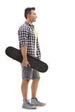 Skater holding a skateboard and waiting in line. Full length profile shot of a skater holding a skateboard and waiting in line isolated on white background Royalty Free Stock Images