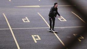 Skater joven en el montar a caballo del casquillo en espacio de estacionamiento patín Manía extrema metrajes