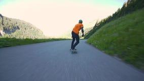 Skater joven masculino profesional que patina cuesta abajo el camino peligroso en paisaje hermoso de la montaña en 4k primer pov metrajes