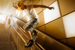 Skater joven que resbala abajo de la barandilla Imagenes de archivo