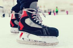 Skater legs at skating rink. Skates black color of. Legs in black pants in ice skating. Amateur sports hobby. old sports hockey skates. on a man`s leg. on the Stock Image