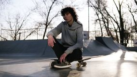 Skater in light grey hoodie sitting on his board looking thoughtful outside the skate park. Sun strongly shines just. Above his head stock video footage